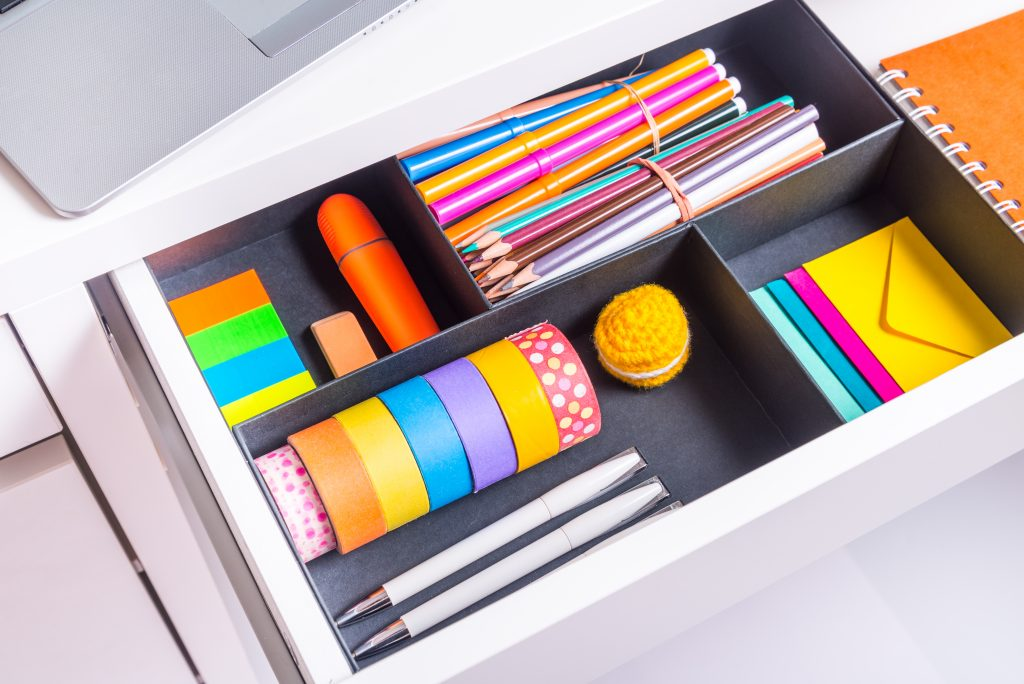 Opened office desk drawer with brightly colored stationery items.